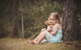Preview wallpaper Blonde child girl, toy, sit under tree