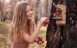 Blonde girl, feeding bird, berries