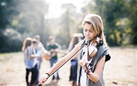 Blonde girl play violin, street