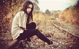 Long hair girl sit on railroad, autumn