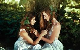 Dos niñas, el bosque, las hojas