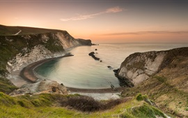Preview wallpaper England, bay, sea, rocks, grass, beach, sunset