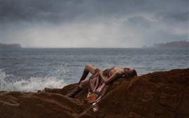 Девочка спит на камне, море