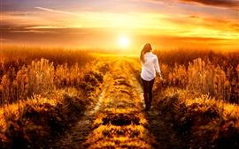Fille à pied sur le terrain, été, coucher de soleil