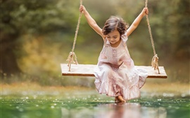 Happy little girl play swing, water