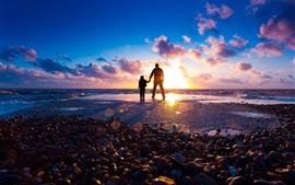 Bebê e seu pai, mar, pedras, por do sol