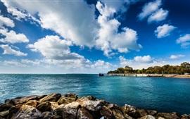 Mar azul, cais, pedras, nuvens