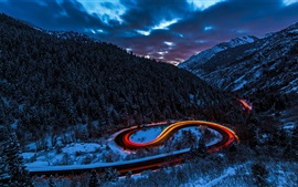 Preview wallpaper Mountains, forest, snow, road, light, car, winter, dusk