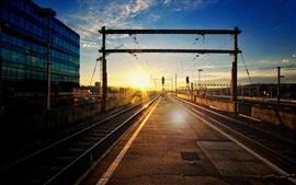 Estación de tren, pista, líneas eléctricas, puesta del sol