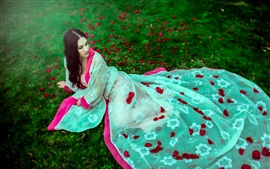 Beautiful dress girl, lying on grass, rose petals