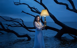 Girl standing in water, lamp, night