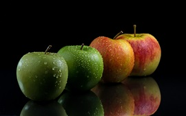 Green and red apples, water drops, black background