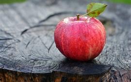 Одно красное яблоко, капли воды, лист, пень