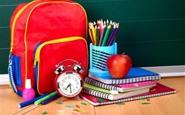 Mochila escolar, reloj despertador, cuaderno, lápices de colores, manzana