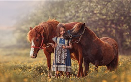 Cute child girl and two brown pony