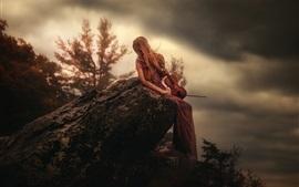 La muchacha se sienta en piedra, violín, tapa de la montaña