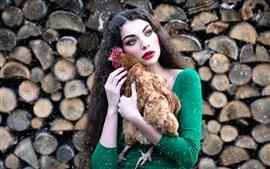 Green skirt girl abraçar uma galinha, maquiagem, nevado