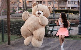 Teddy bear and girl play swing