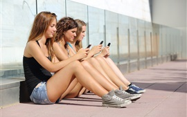 Preview wallpaper Three girls sit to use phones