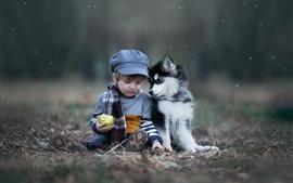 Chico lindo niño y perro, manzana verde, nieve
