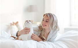 Preview wallpaper Happy blonde girl and cat in bed