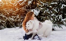 Menina feliz e cachorro branco na neve, inverno