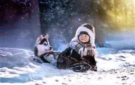 Child and husky dog in winter, snow