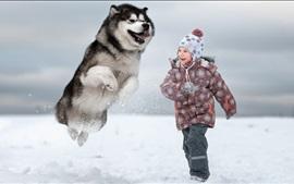 Девочка и собака играют в снегу