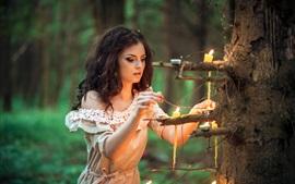 Chica de pelo rizado, velas, bosque
