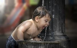 Mignon petit garçon joue de l'eau