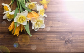 Daffodils, tulips, wood desktop