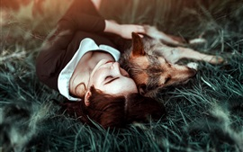 Girl and dog sleep on grass