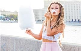 Chica comer algodón de azúcar, falda, trenzas