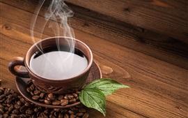 Um copo de café, vapor, grão de café, folha