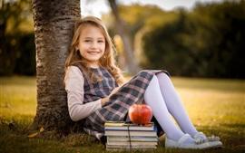 Sorria criança garota, loira, livros, maçã