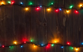Colorful holiday lights, wood board