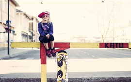 Cute little girl, glasses, fence, skateboard, street