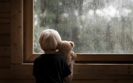 Little boy and teddy bear look at window, rainy