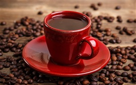 Um copo vermelho café, grãos de café
