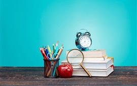 Ainda vida, livros, lupa, tesoura, despertador, maçã vermelha, fundo azul