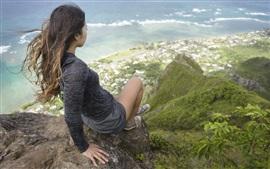 La muchacha asiática se sienta en la cima de la montaña