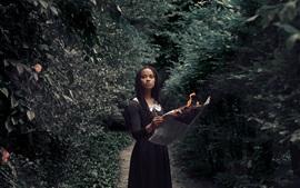 Black skirt girl read newspaper, fire, trees