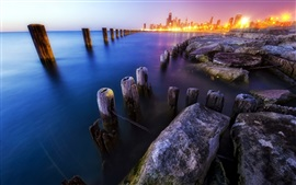 Preview wallpaper City, coast, evening, stumps, rocks, skyscrapers, lights