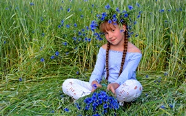 Cute child girl, blue flowers, grass