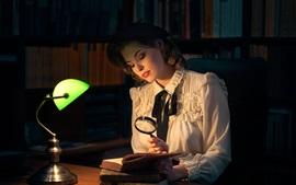 Livro de leitura de menina, lâmpada, lupa