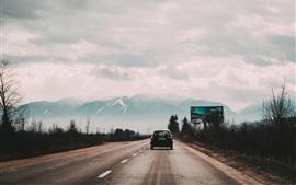 Opinião traseira do carro preto de Honda, estrada, montanhas