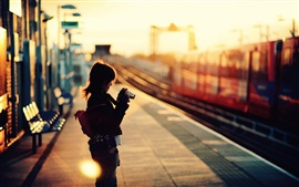 Preview wallpaper Little girl use camera, rail station, sunset