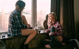 Dos chicas se sientan en el alféizar de la ventana