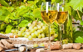 Two glass cups of white wine, green grapes