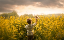 Preview wallpaper Child, little boy play toy plane in the rapeseed flowers field